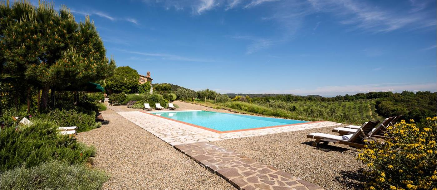 Pool with patio area, sun loungers, plants, trees, flowers and countryside view at Villa San Barberino in Tuscany, Italy