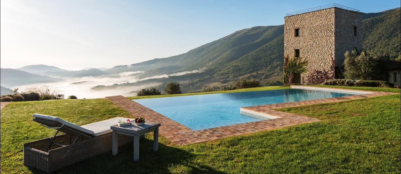 Pool with sun lounger, coffee table, fruit, green grass and view of mountains and villa at Bel Canto in Umbria, Italy