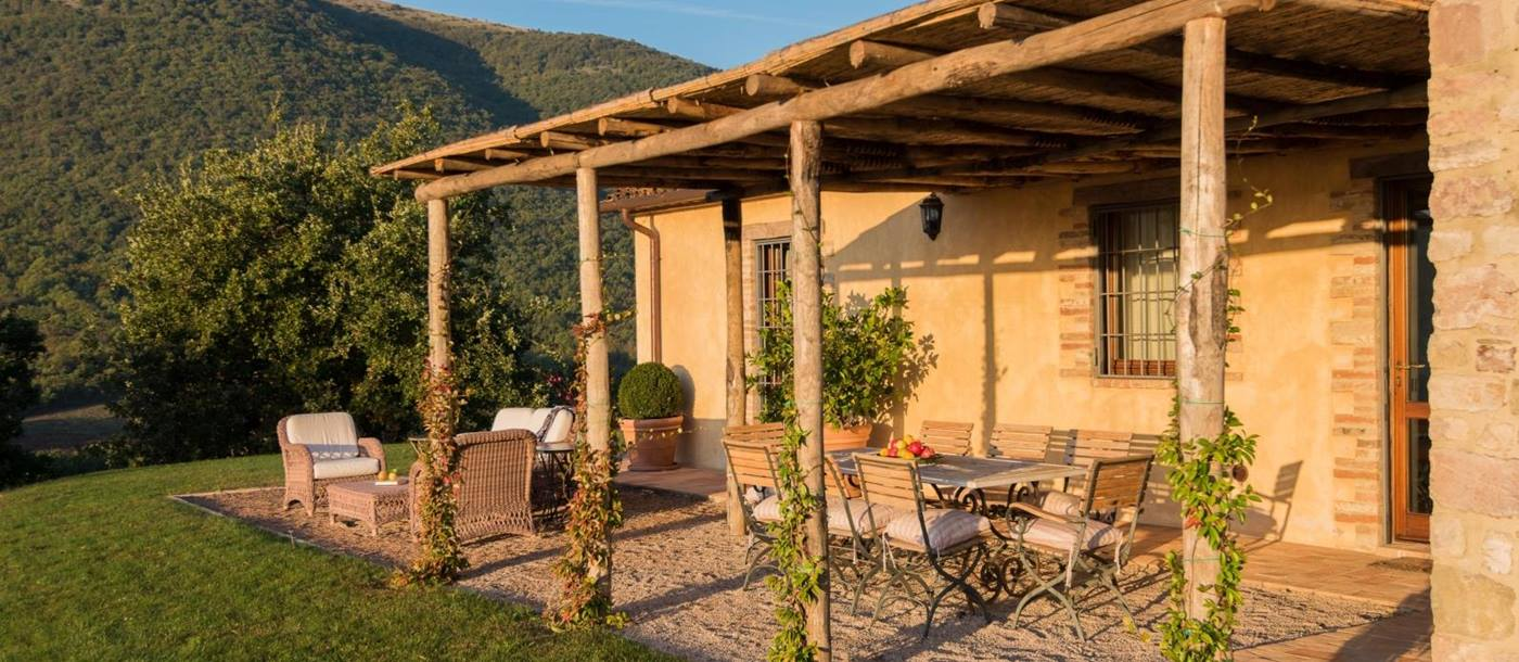 Patio with covered dining area, table, chairs, fruit, plants, comfy chairs and mountain view at Bel Canto in Umbria, Italy