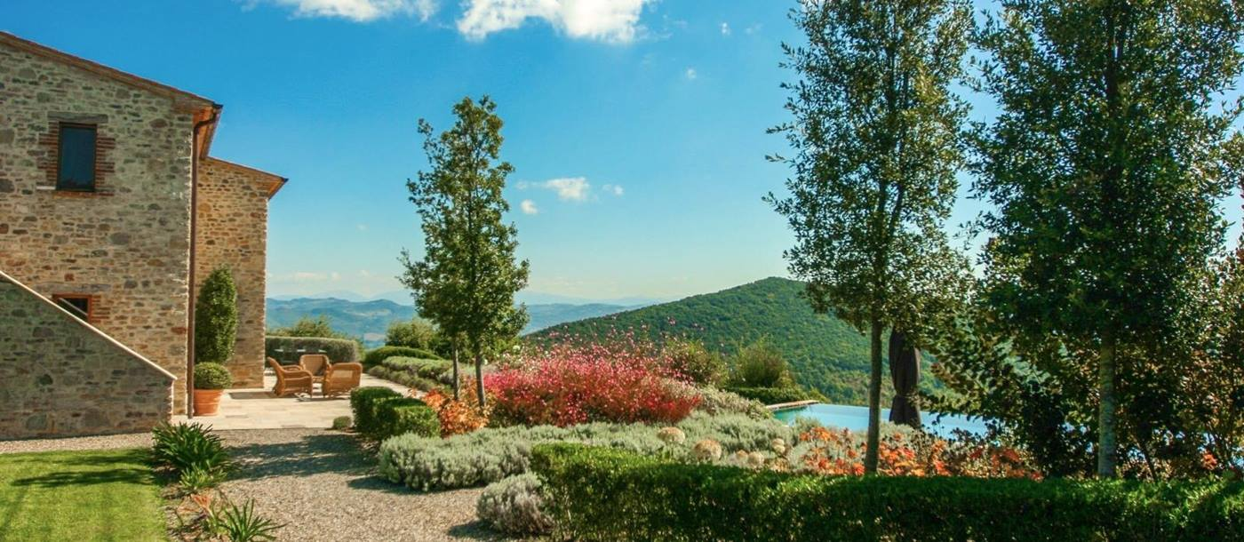 Garden with flowers, trees, hedges, terrace, pool and countryside views at Monticello in Umbria, Italy