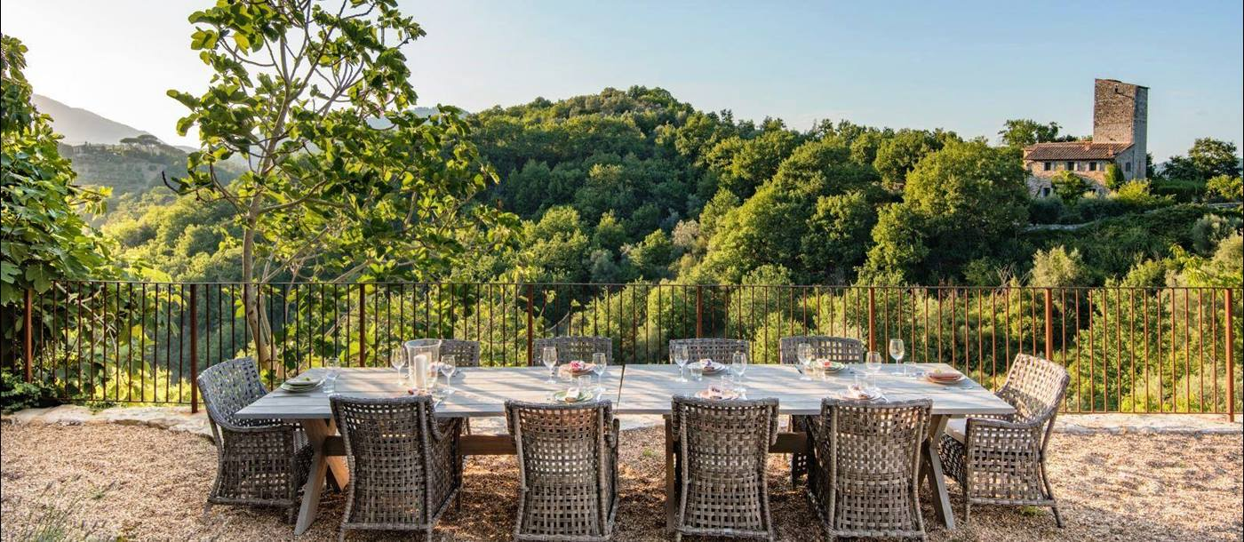 outdoor dining area with long wooden table with 10 wicker chairs at villa del conte in umbria, Italy with view of hills