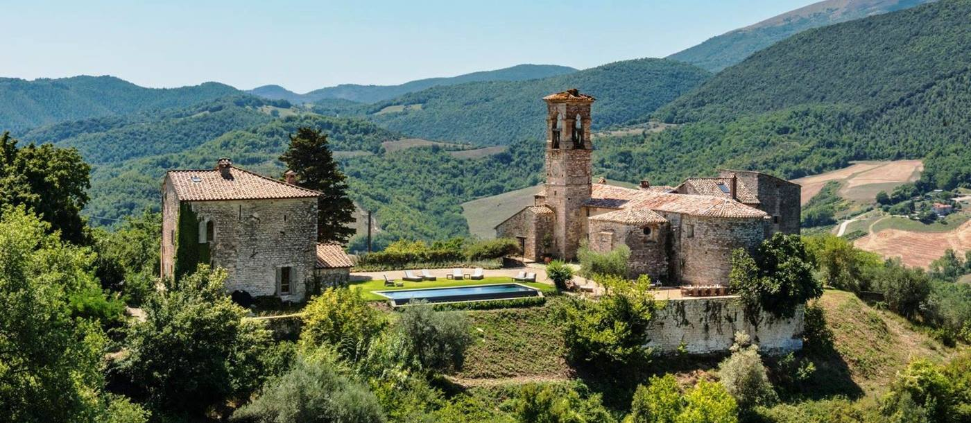 panoramic view of villa del conte in umbria, Italy with green wooded hills in the background