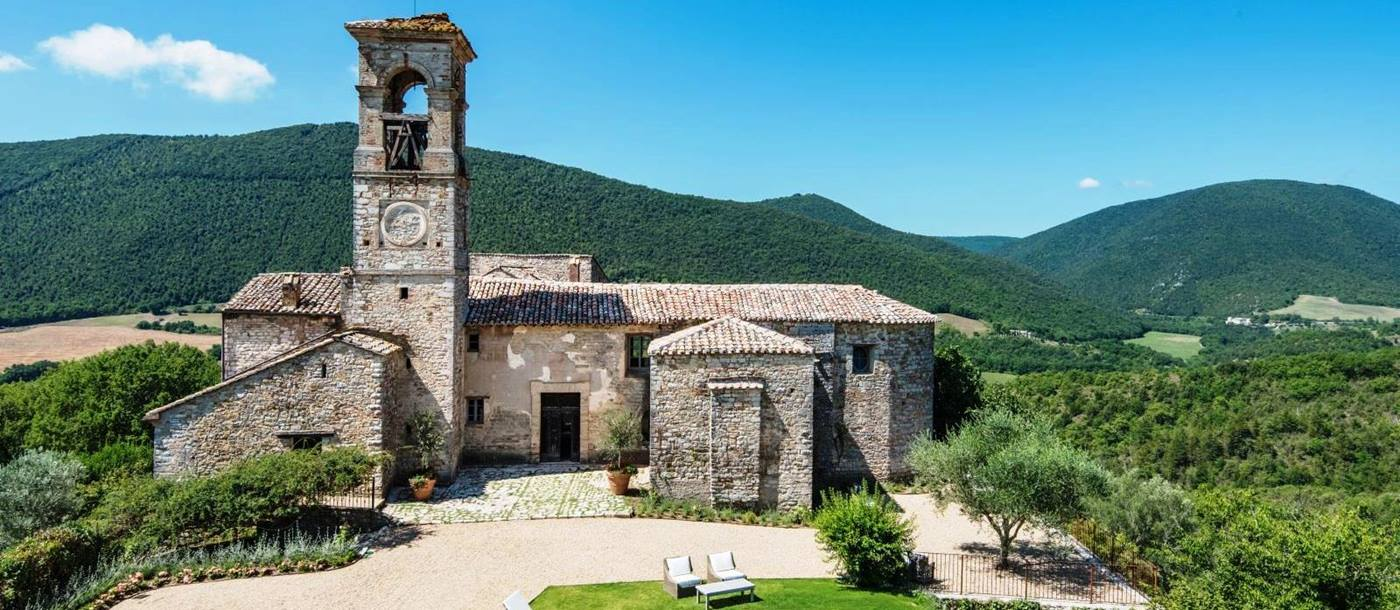 old stone buildings of villa del conte in umbria, Italy with 5 white sunbeds next to pool in front of gravel drive