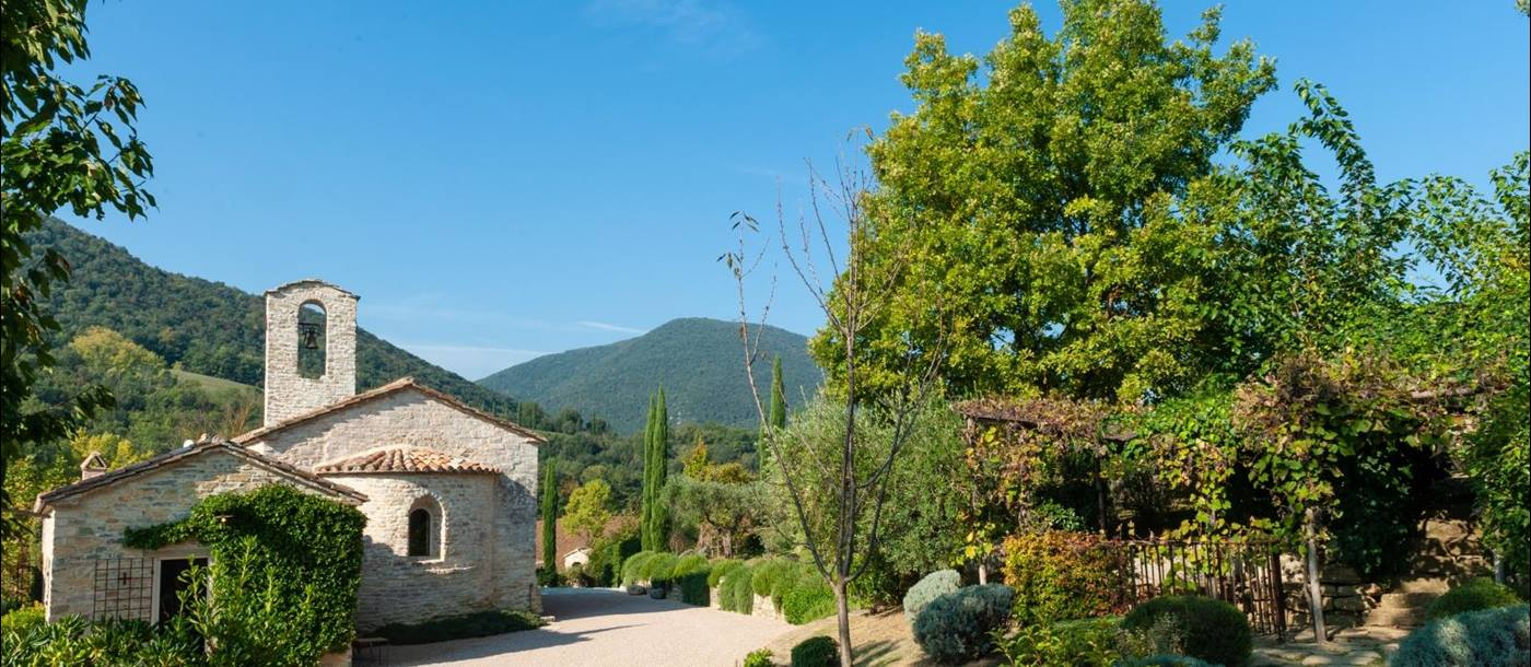 Exterior of villa & garden with pathway, plants, trees and view of surrounding hills at Villa Il Carmine in Umbria, Italy