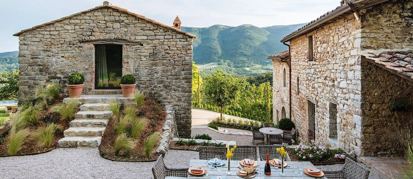 Outdoor dining table with house and annex behind and view of mountains at Villa Piuma in Umbria, Italy