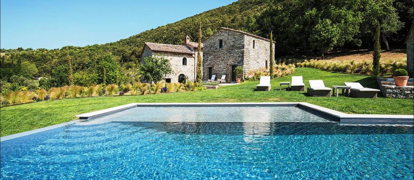 View over the swimming pool with sunbeds and Villa Piuma in Umbria in the background