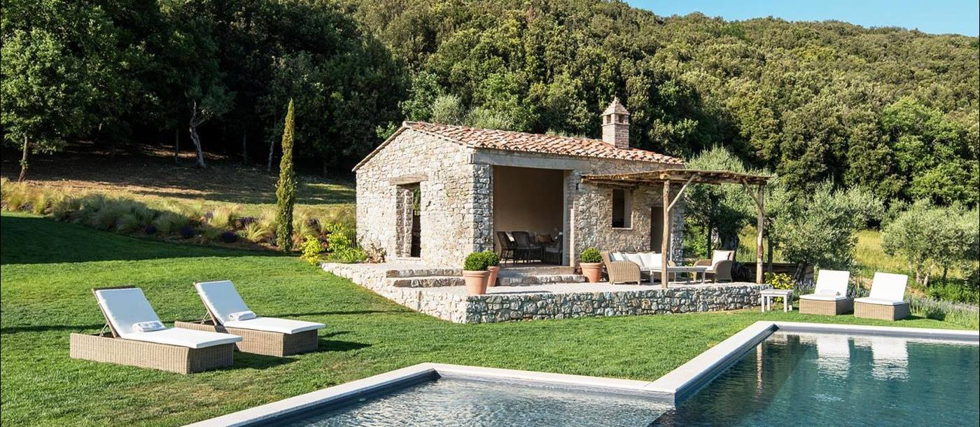 Pool house at Villa Piuma in Umbria, Italy with pool and sunbeds in front and woods behind