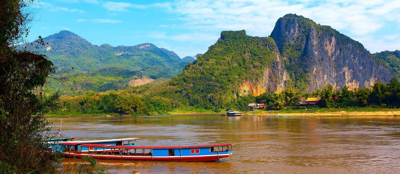 A brightly painted boat crusing down the Mekong in Laos