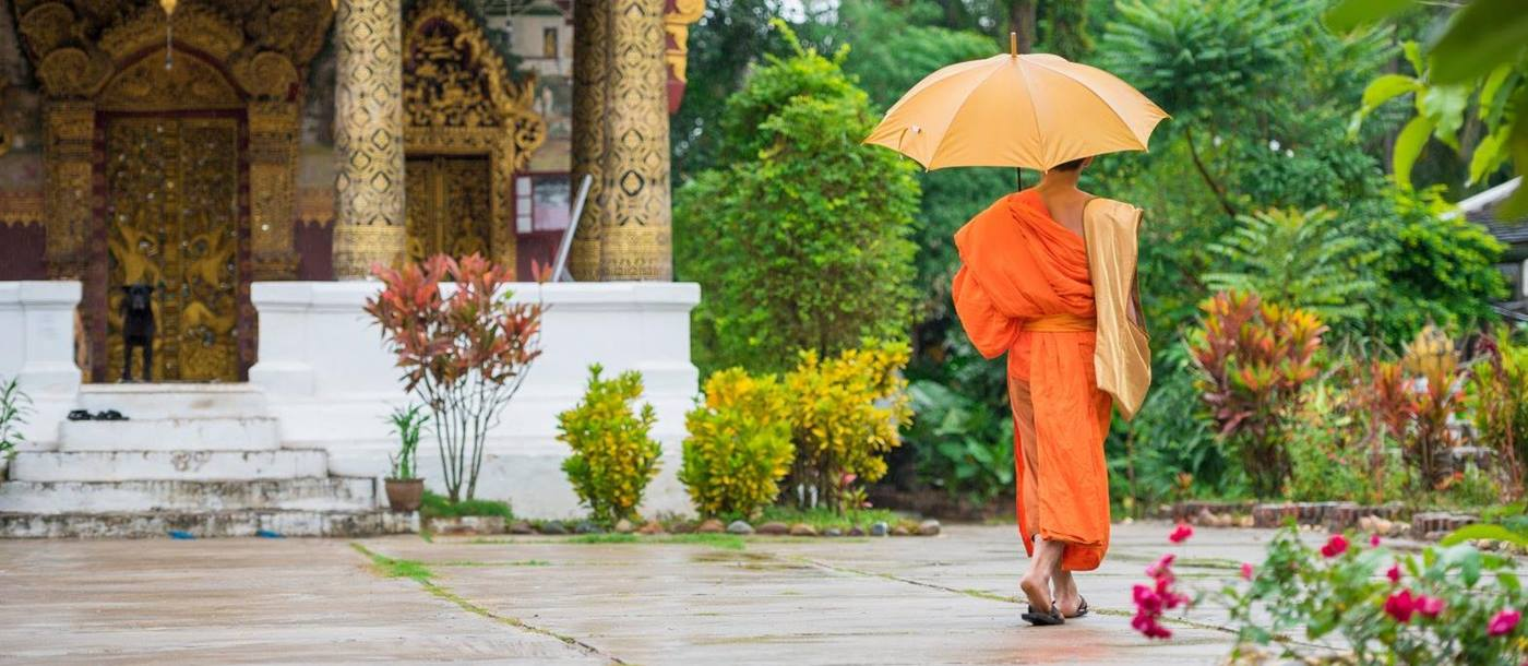 Buddhist monk in traditional dress approaching a temple in Laos