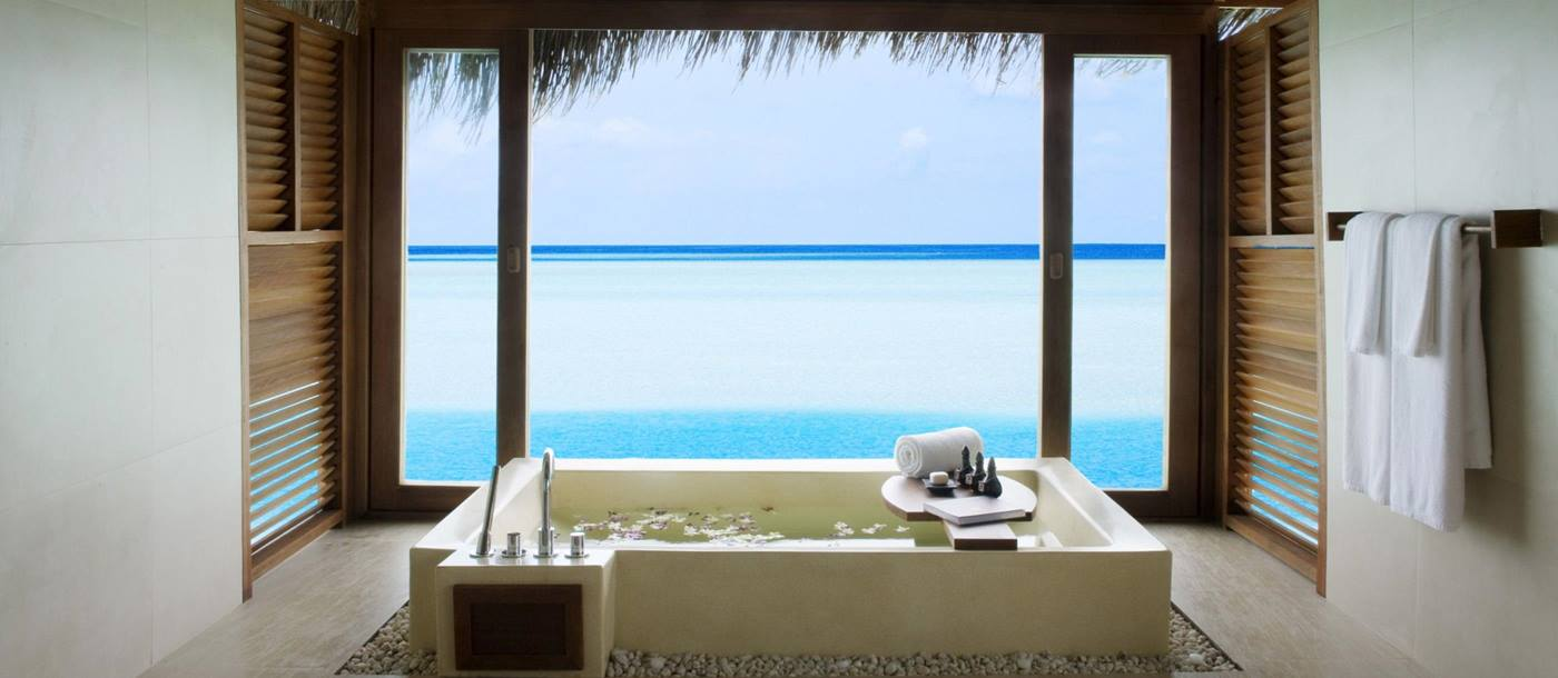 The bathroom of an overwater suite at Anantara Dhigu