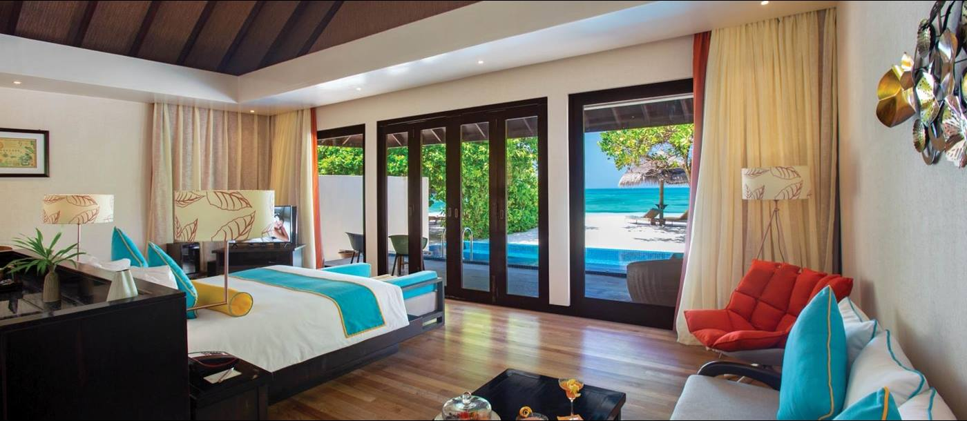 Interior of a Sunset Pool Villa with views over the private pool, white sand beach and Indian Ocean at luxury resort Atmosphere Kanifushi in the Maldives