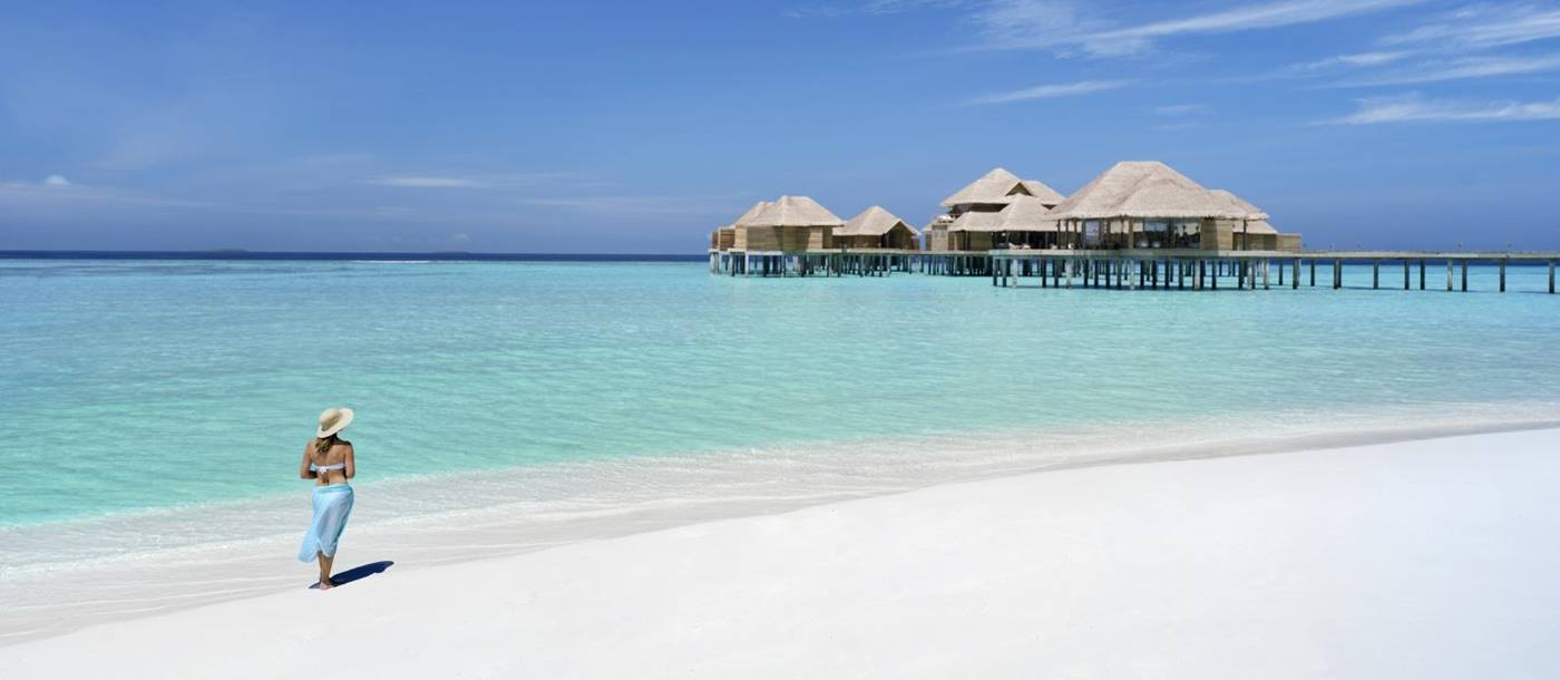 Woman walking on the white sand beach at luxury resort Vakkaru in the Maldives