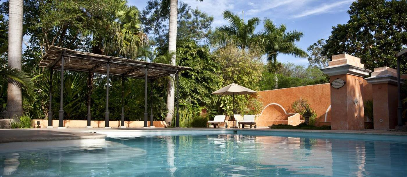 A view across the pool at the small luxury hotel Hacienda Xcanatun in Mexico