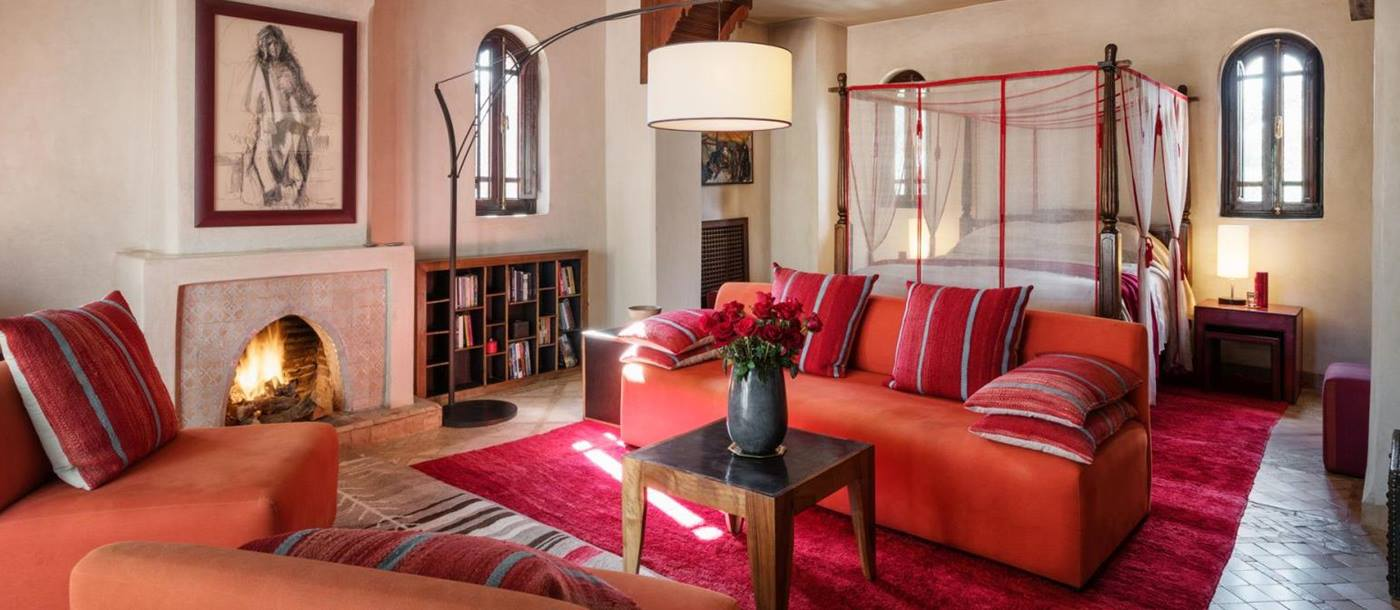 The Perla Suite with four poster bed, sofa, chairs and an open fire at Dar Zemora in Morocco