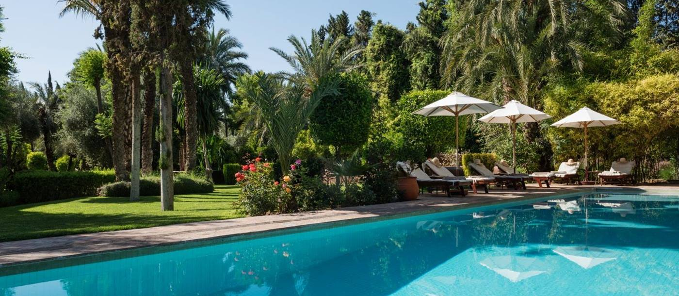 The pool, set in lush green gardens, with sunbeds and sun umbrellas at Dar Zemora in Morocco