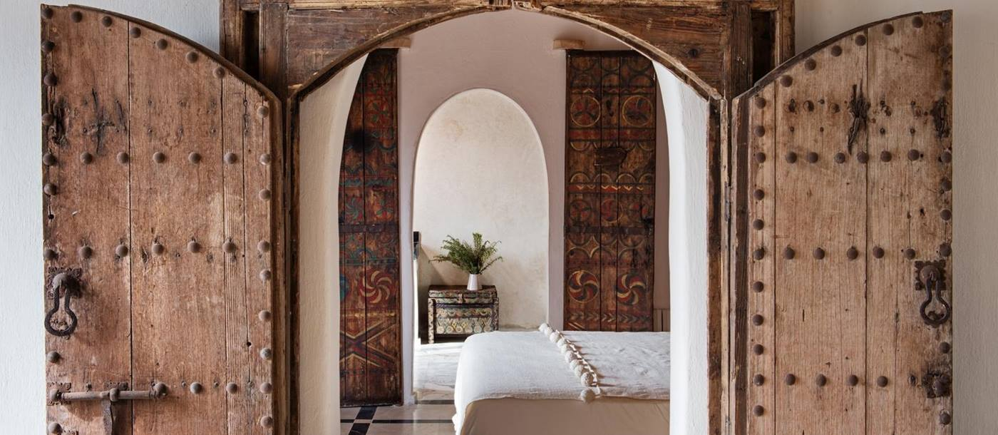 Artisically carved door frame leading to a bedroom