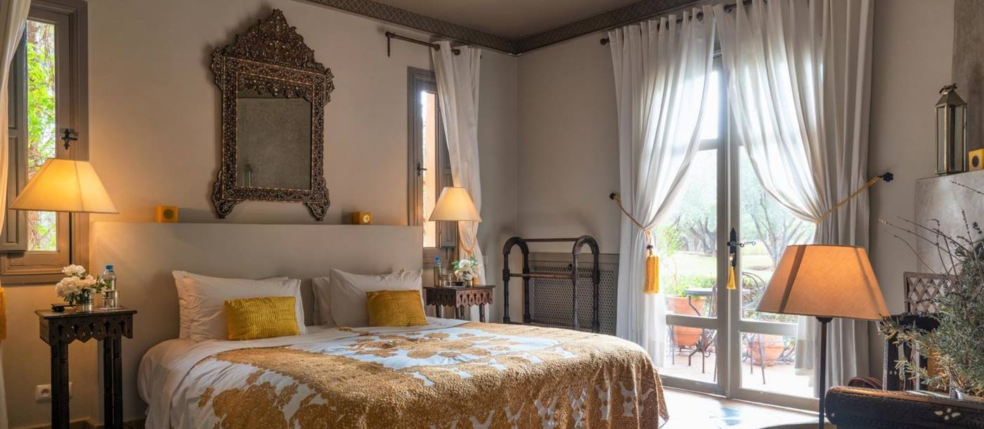 Bedroom with yellow double bed, armchair, bedside tables, lamps, mirror and French doors at Dar Arbala in Morocco