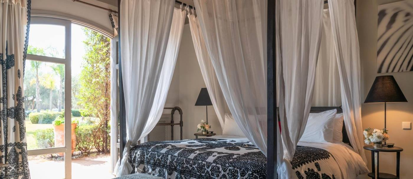 Bedroom with four poster double bed, stools, bedside tables, lamps and French doors at Dar Arbala in Morocco