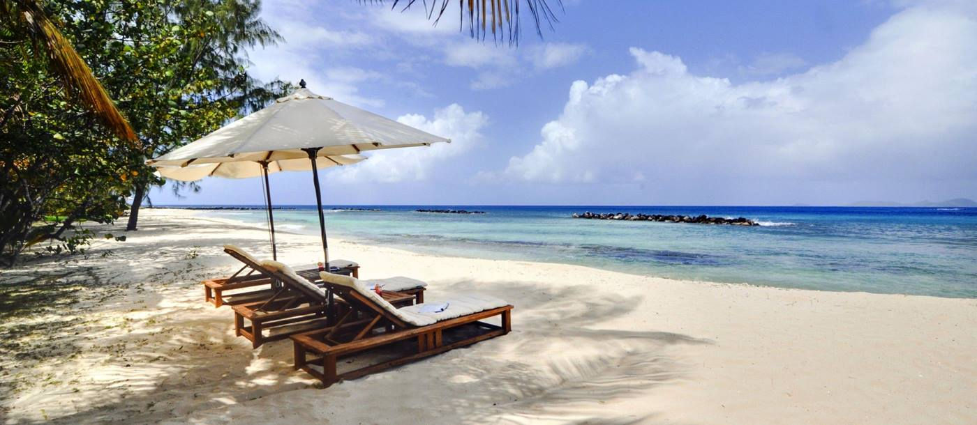 The beach and three sun loungers at Gingerbread, Mustique