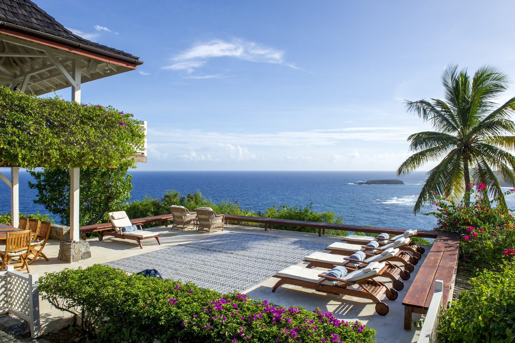 Terrace with sun loungers at Pangolin, Mustique