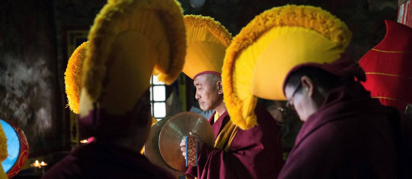 Buddhist monks adorned in vibrant yellow headpieces