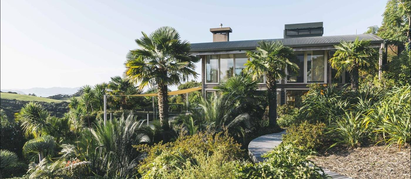 First Light Temple villa New Zealand exterior with native bushes and palm trees
