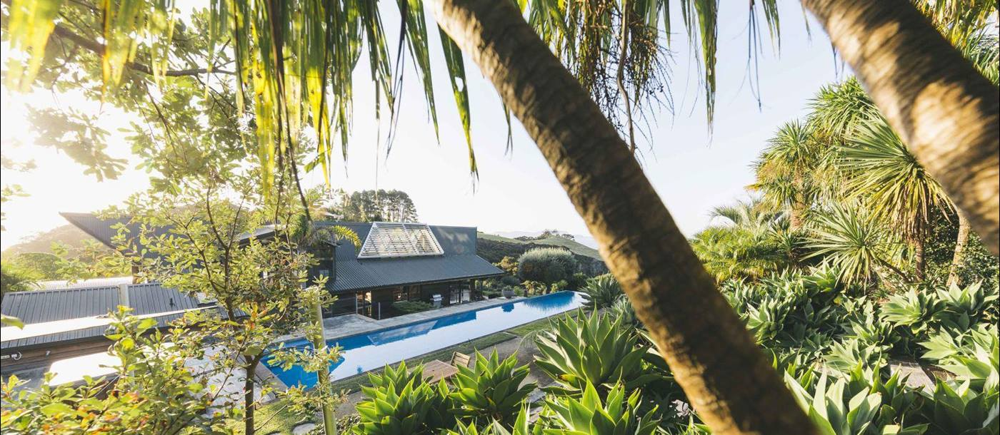 Sacred Space villa New Zealand exterior with palm trees and a pool