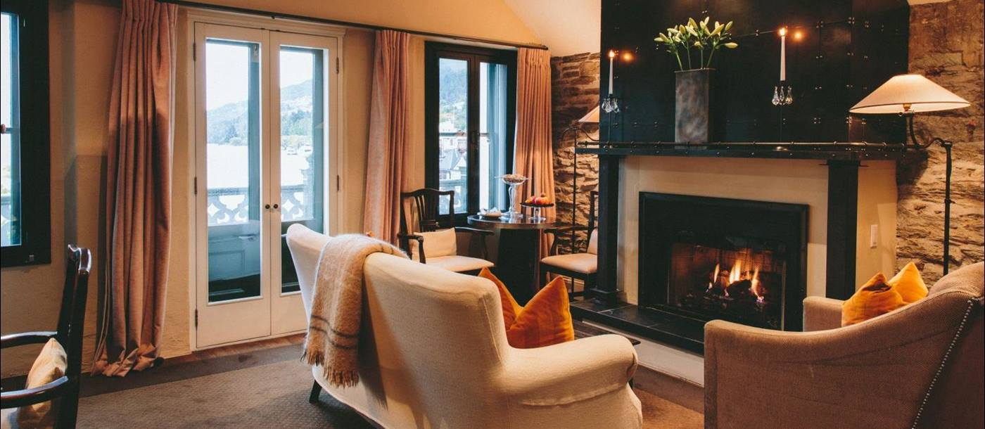 Eichardt's Private Hotel New Zealand suite with a glowing fire in the fireplace and a sofa