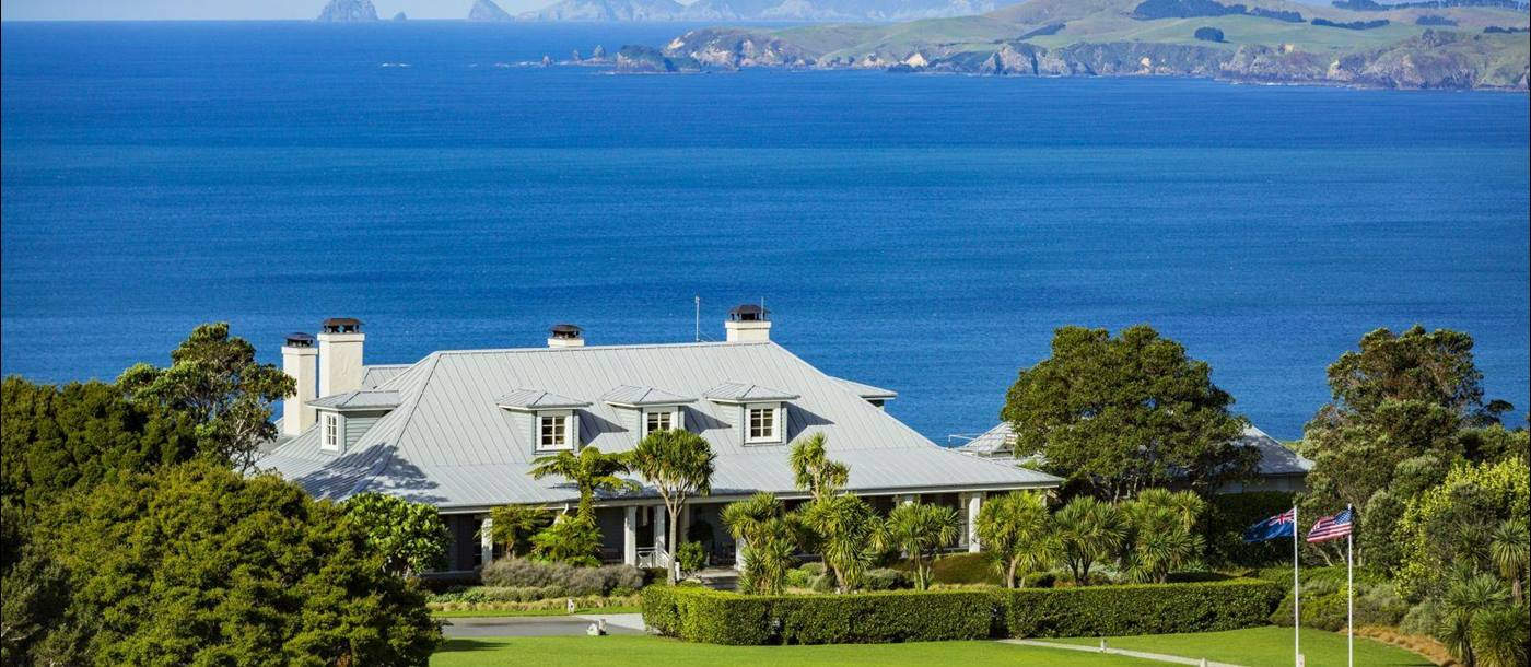 Exterior shot of Kauri Cliffs Lodge in New Zealand with green lawns in front and the Pacific Ocean and mountains in the background