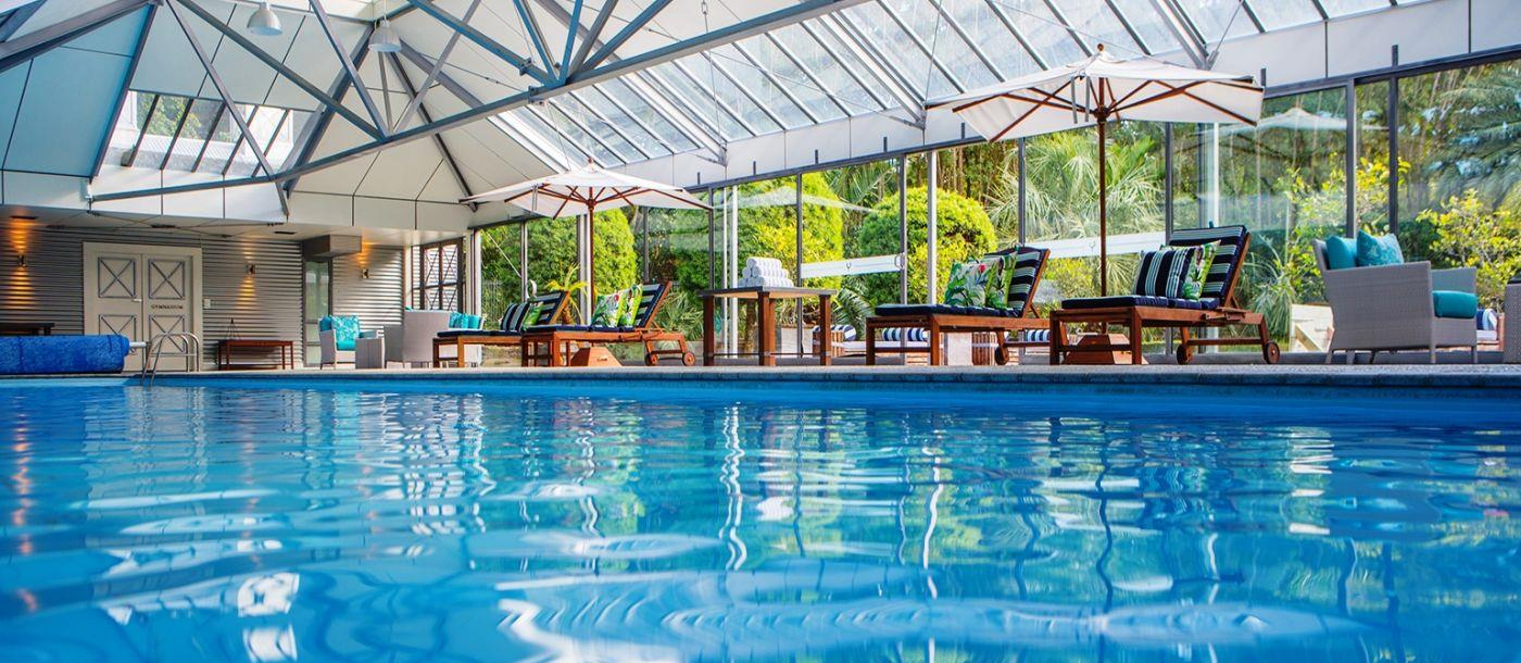The swimming pool with sunbeds, chairs and tables in the covered spa at Wharekauhau luxury lodge in New Zealand