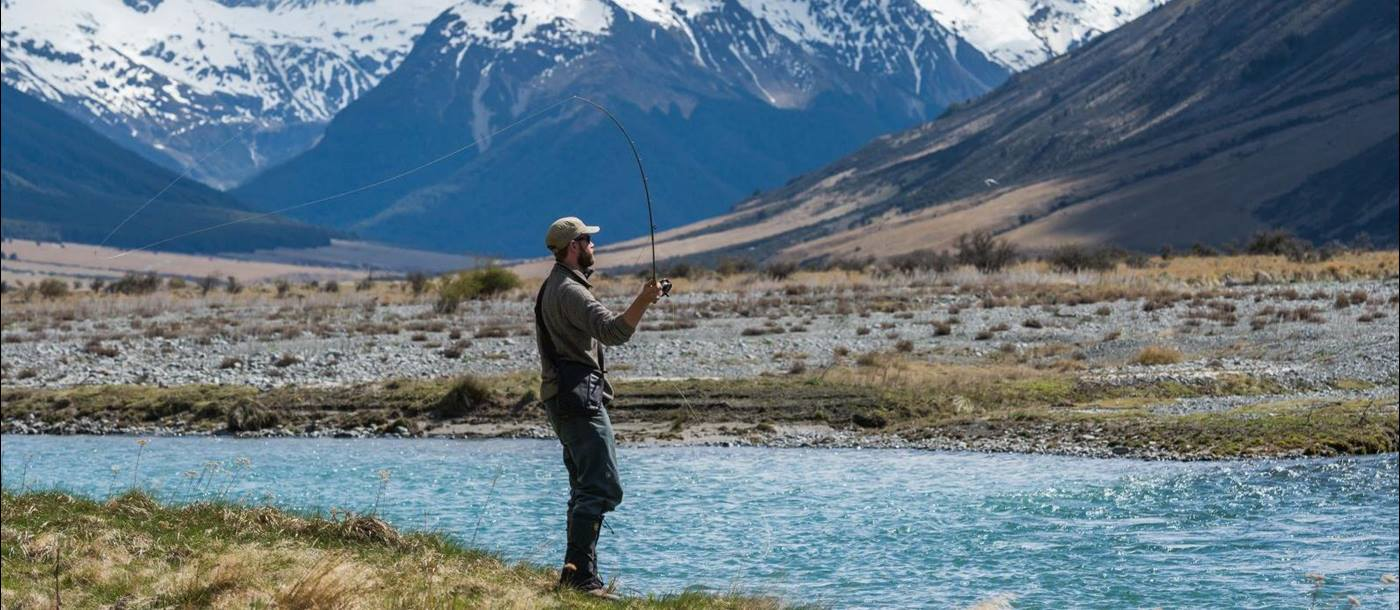 A man fly fishing on the edge of the Ahuriri River at The Lindis Lodge in New Zealand