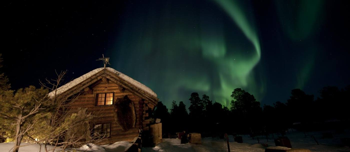 Northern lights above lodge at Engholm Husky Design Lodge in Norway