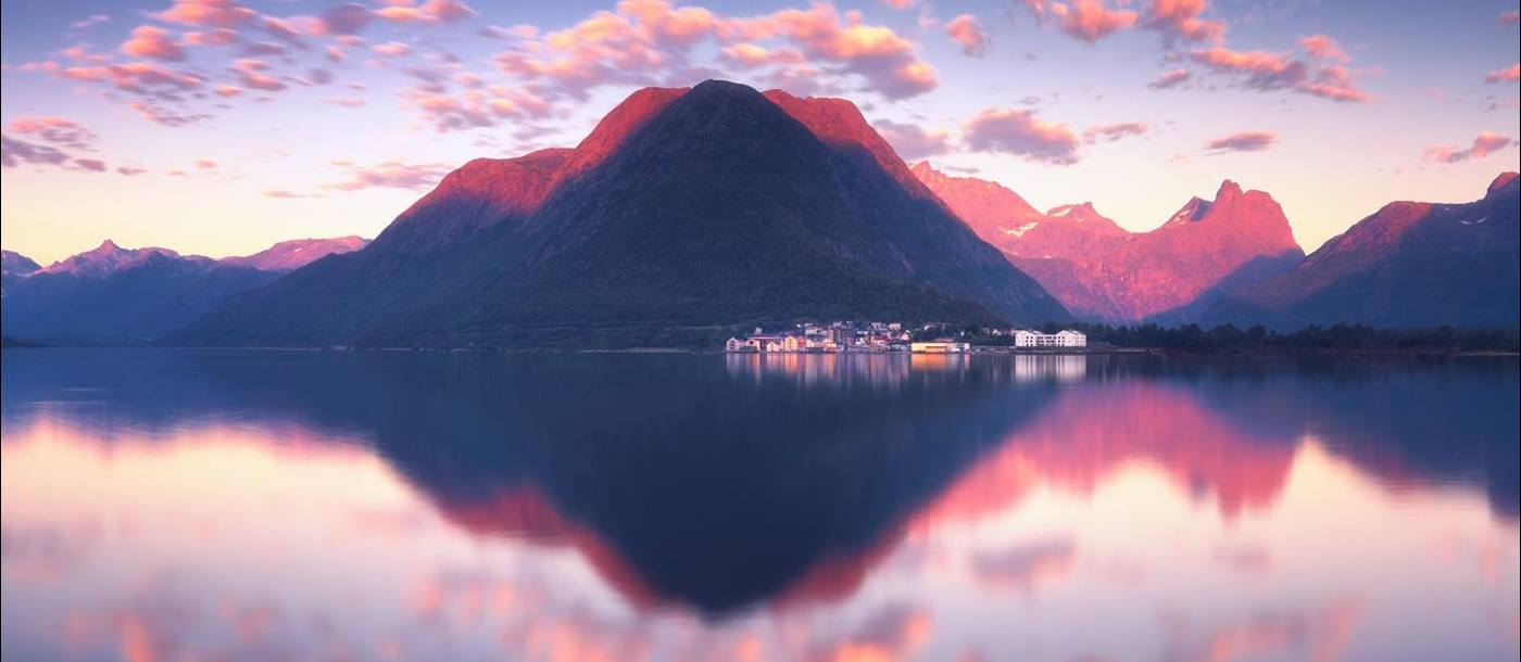 Reflections of the mountains in still waters in Romsdalfjord Norway