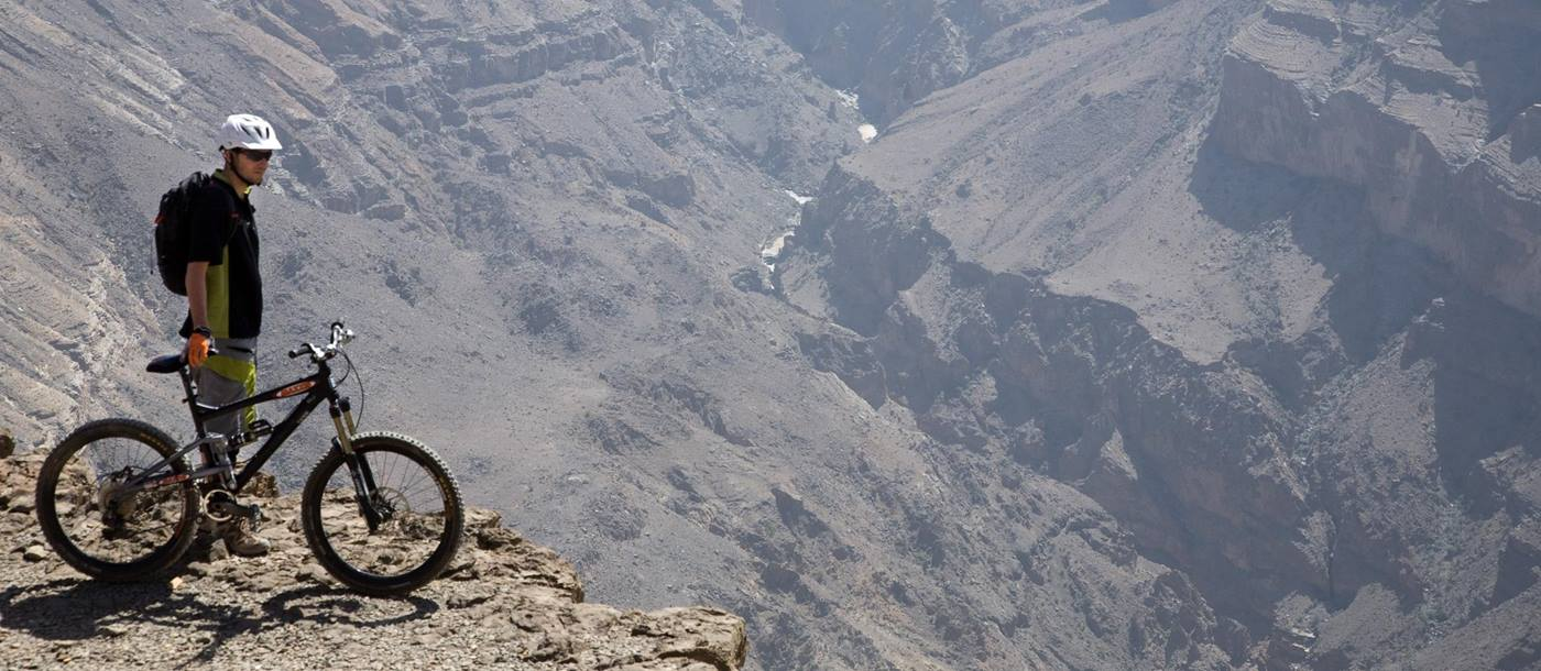 A biker overlooking a canyon near The View, Oman