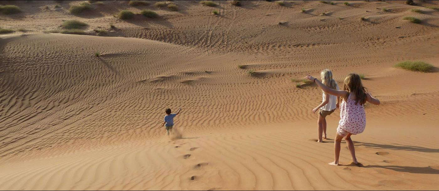 Children running down the dunes in Oman