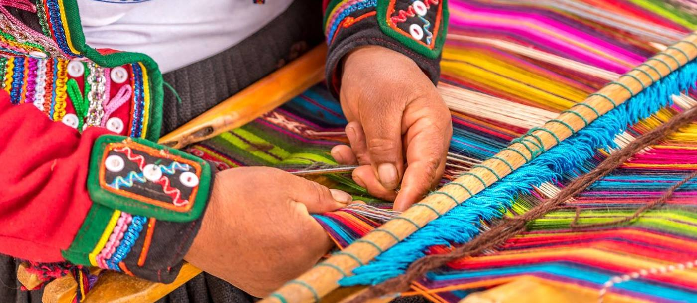 Peruvian lady in traditional dress weaving colourful textiles in the Sacred Valley of the Incas