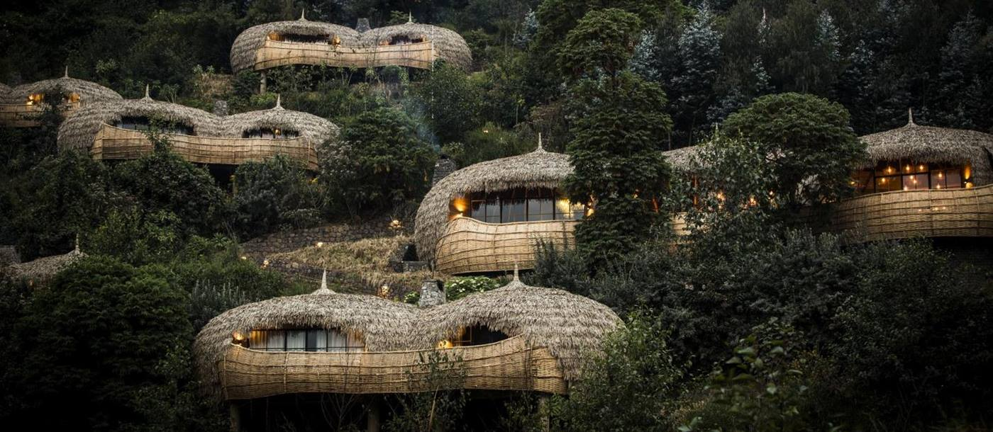 A view of the exterior of thatched bamboo villas set in the hillside at Bisate Lodge in Rwanda
