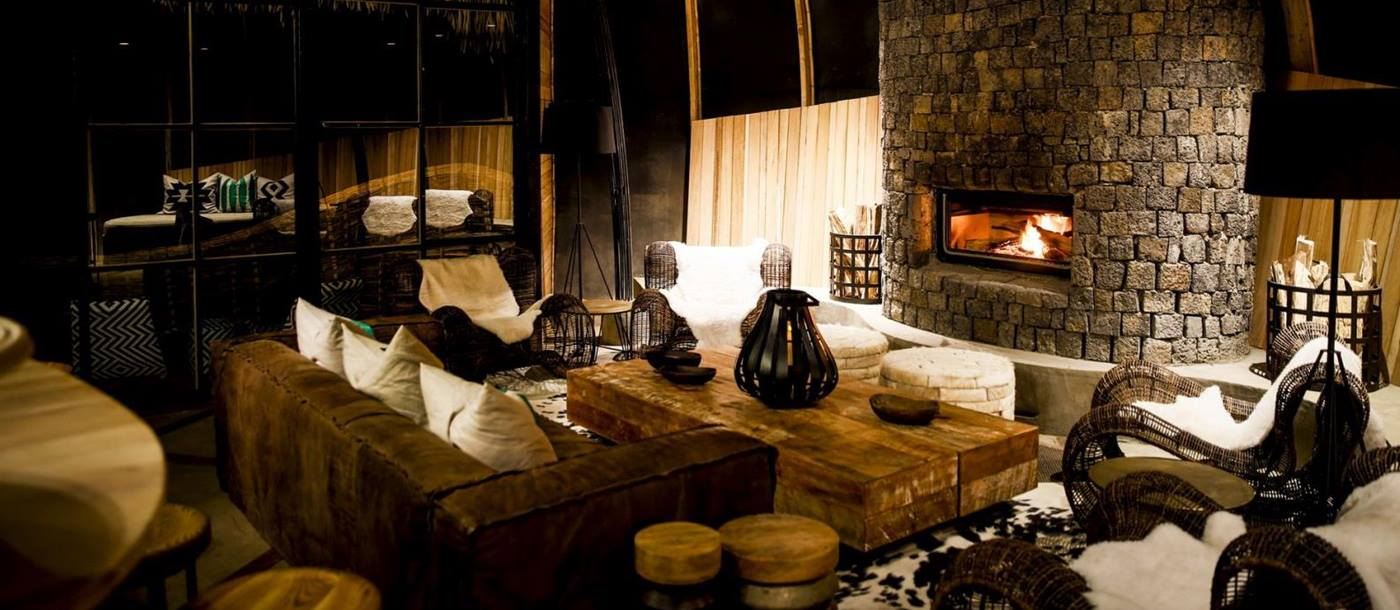 The interior of a room with comfy sofa, chairs, table and a big stone fireplace at Bisate Lodge in Rwanda