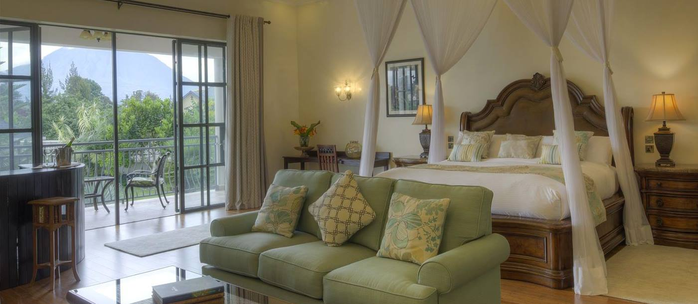A bedroom suite with double bed, sofa, table, corner bar and outdoor balcony with a table and chairs at The Bishops House hotel in Rwanda