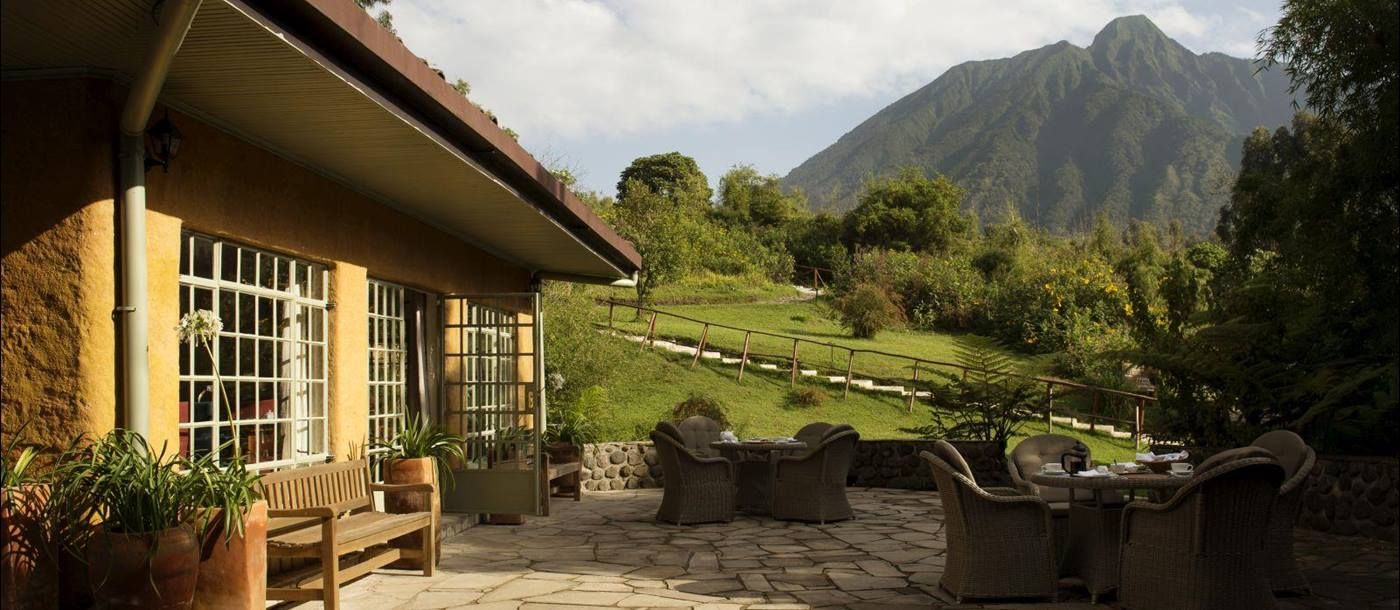 The outside patio with wicker furniture at Sabyinyo Silverback Lodge in Rwanda with a view of the mountains in the background