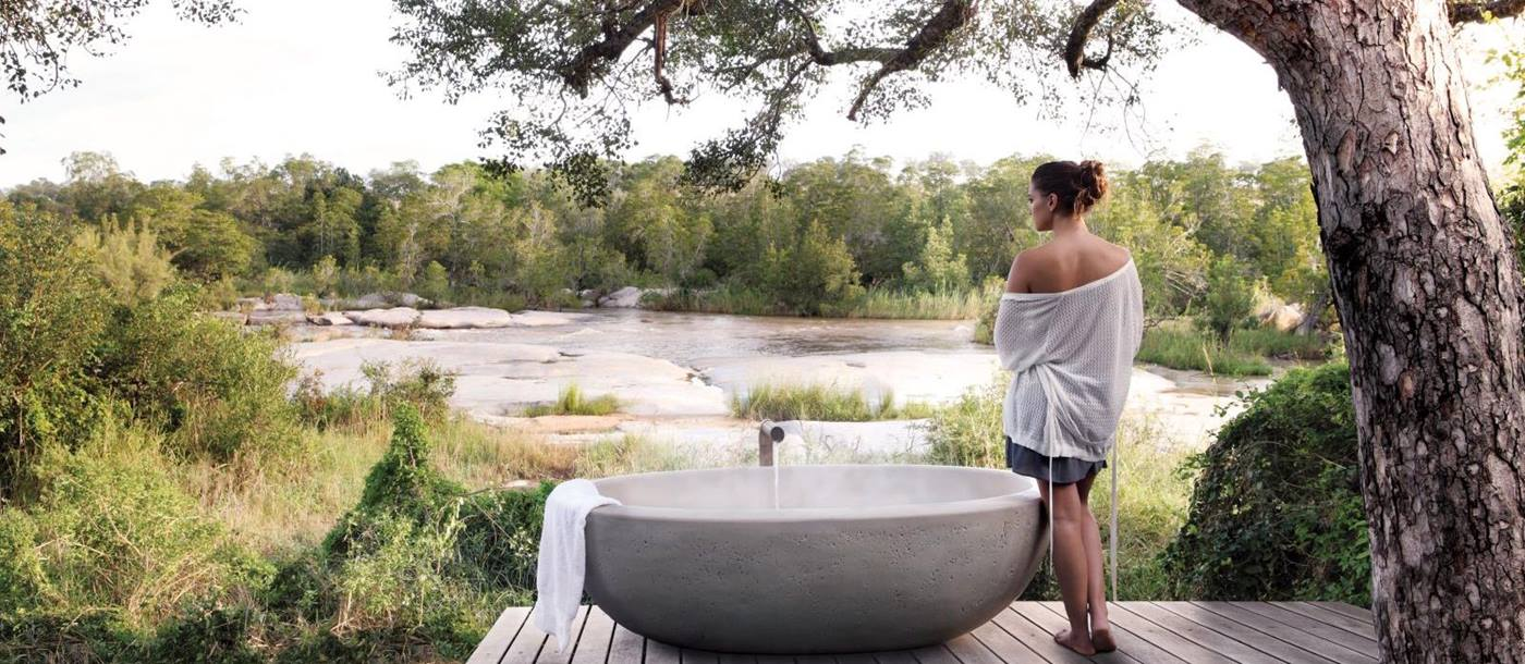 Outdoor bath with river view at Londolozi Granite Suites in South Africa