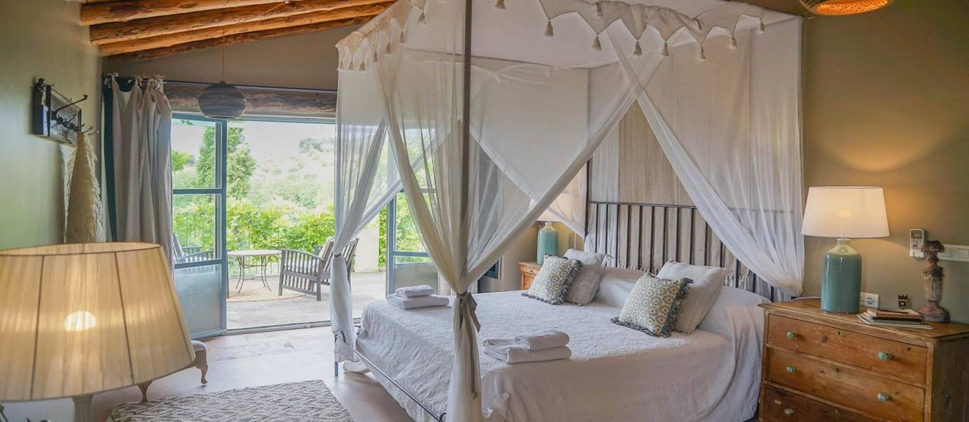 Master bedroom with four poster bed and extensive swing doors to a private terrace at luxury villa Pero di Ronda in Spain