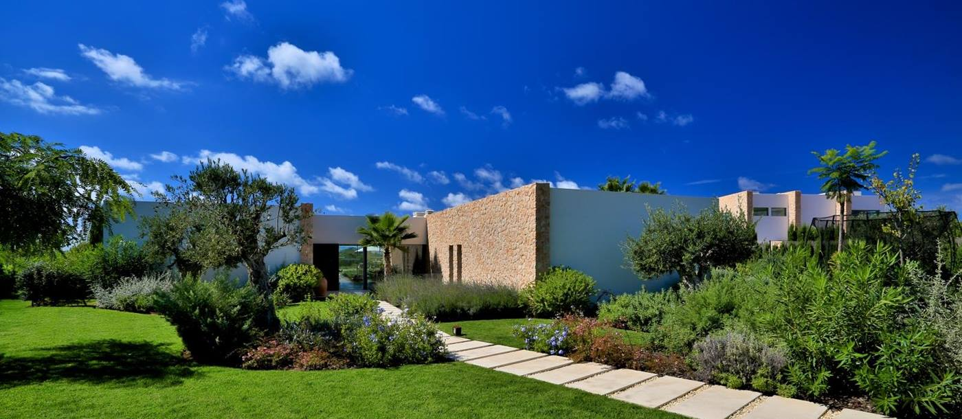 Front garden with green grass, trees, flowers and plants at Cala Comte in Ibiza, Spain