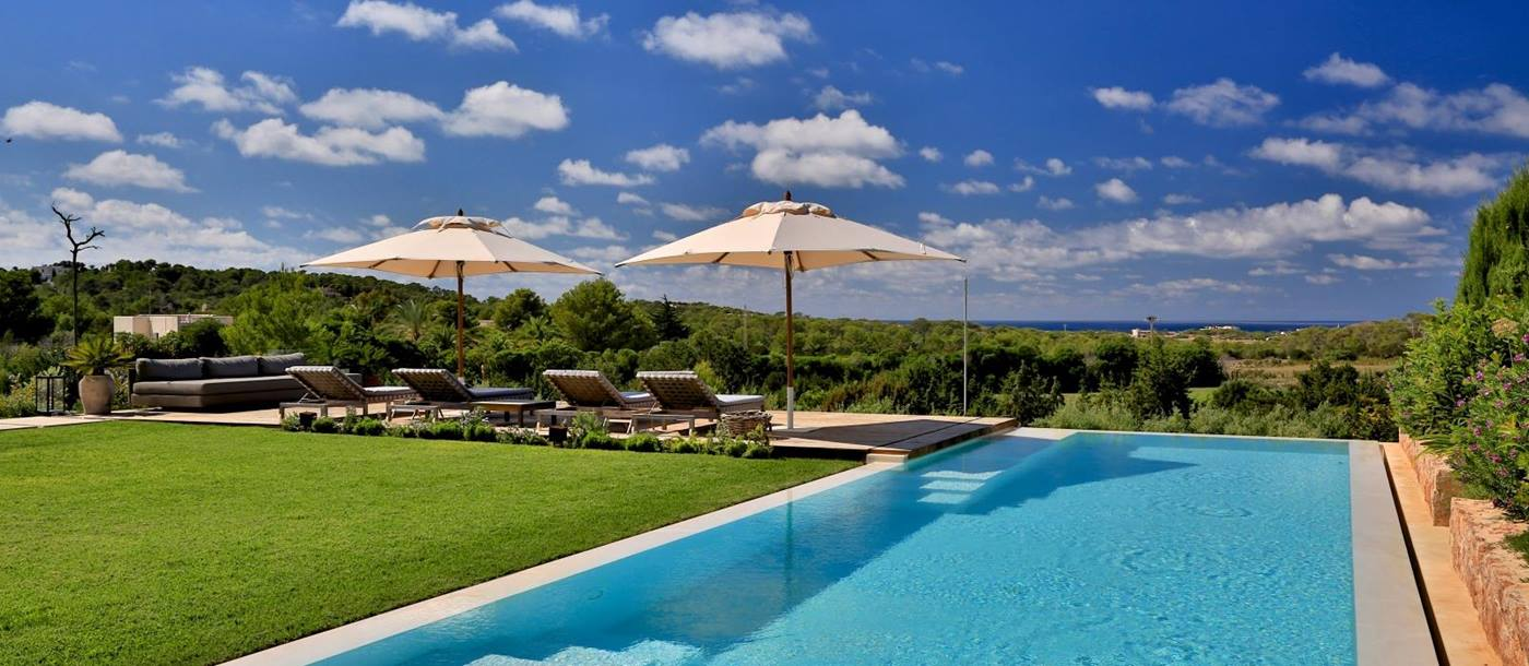 Pool and garden with sun loungers, umbrellas and sea view at Cala Comte in Ibiza, Spain