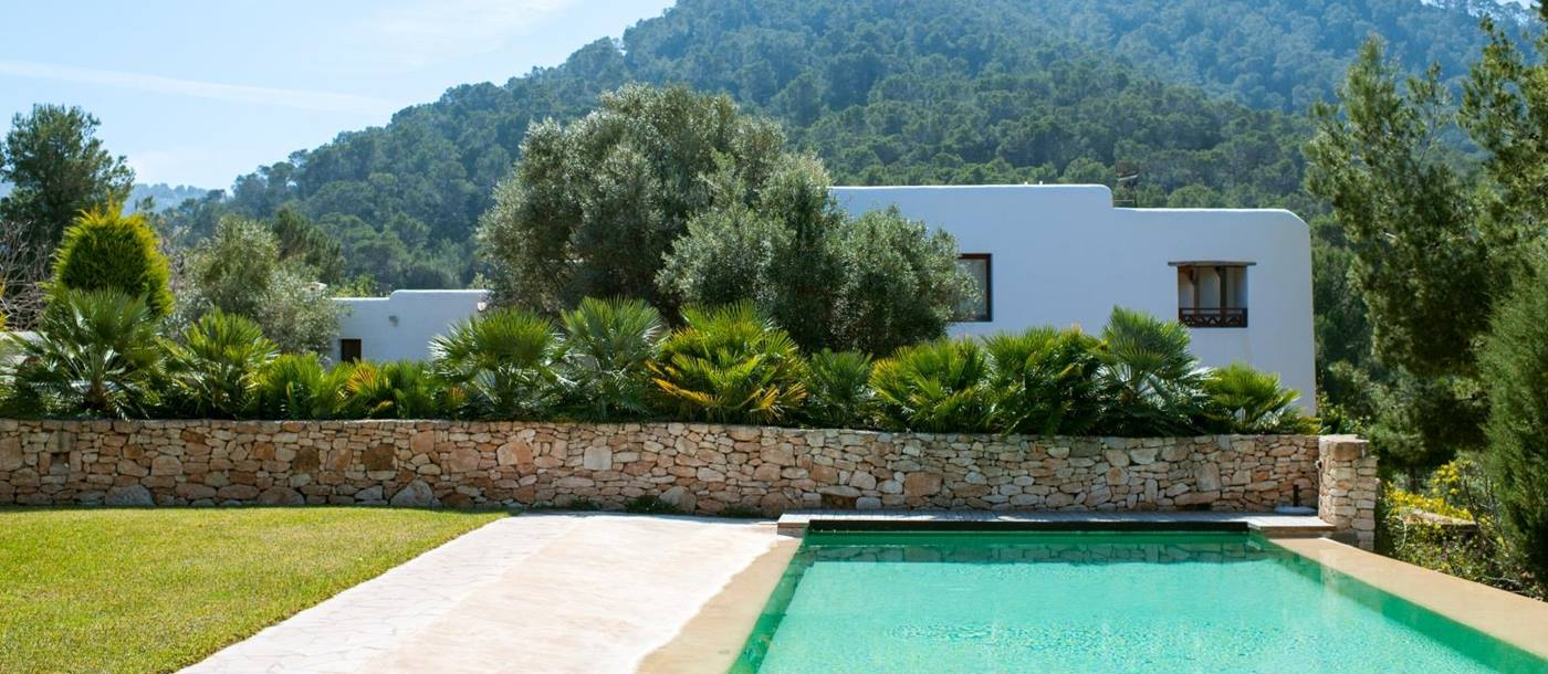 Pool area with grass and view of villa and surrounding hills at Casa Sabena on Ibiza, Spain