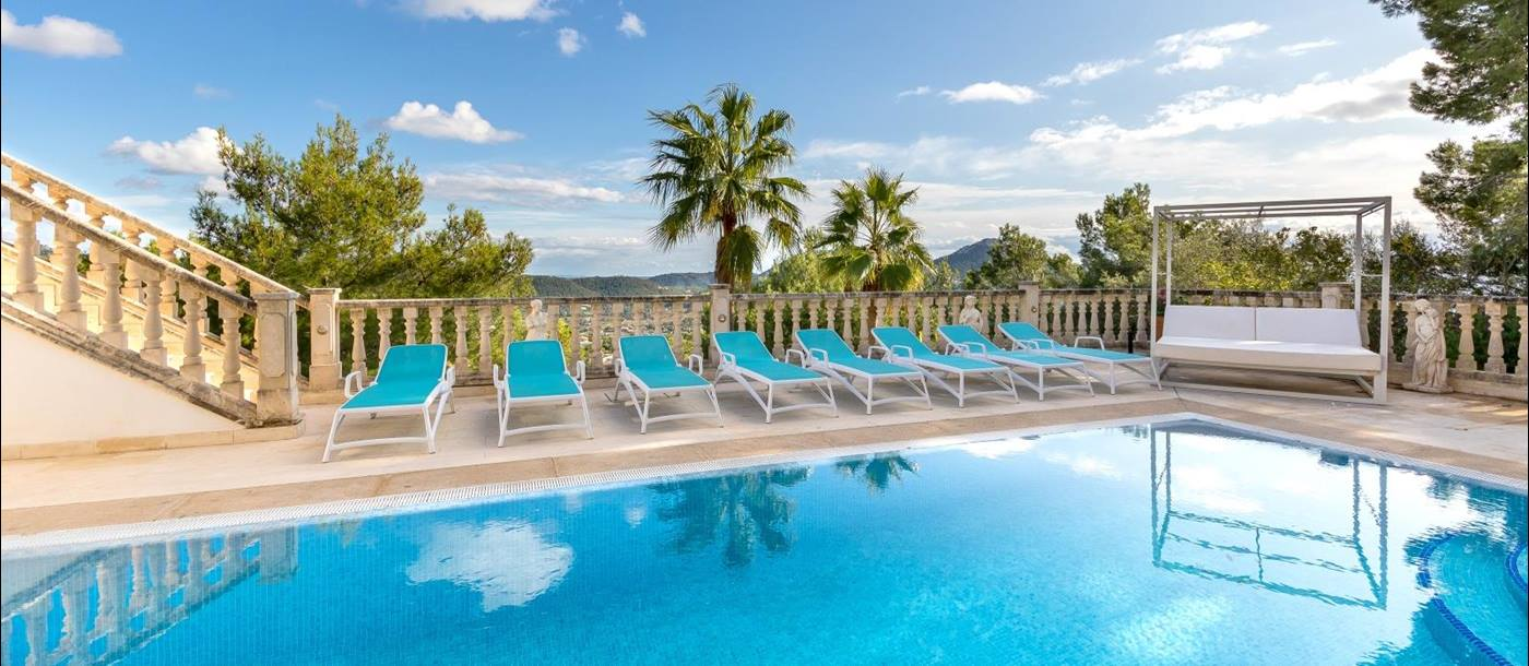 Pool area with sun loungers, day bed, palm trees and mountain view at Casa Verano in Mallorca, Spain