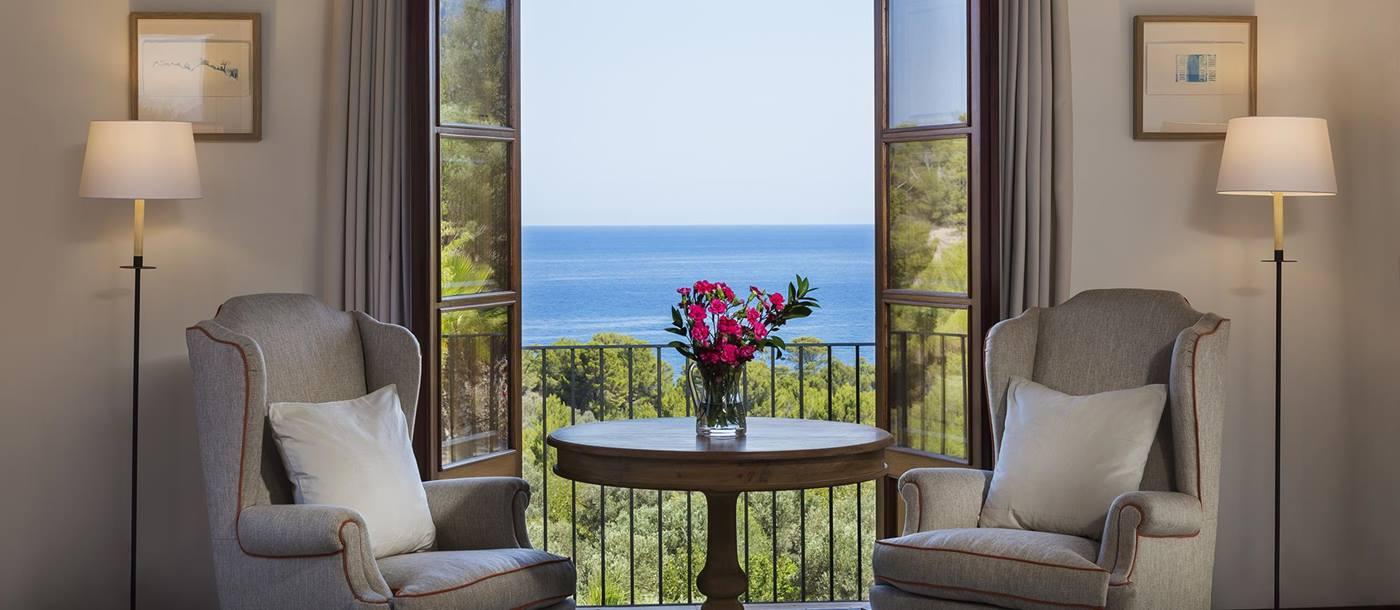 two chairs and round table in front of a large window at  villa Sa Rotja in Mallorca