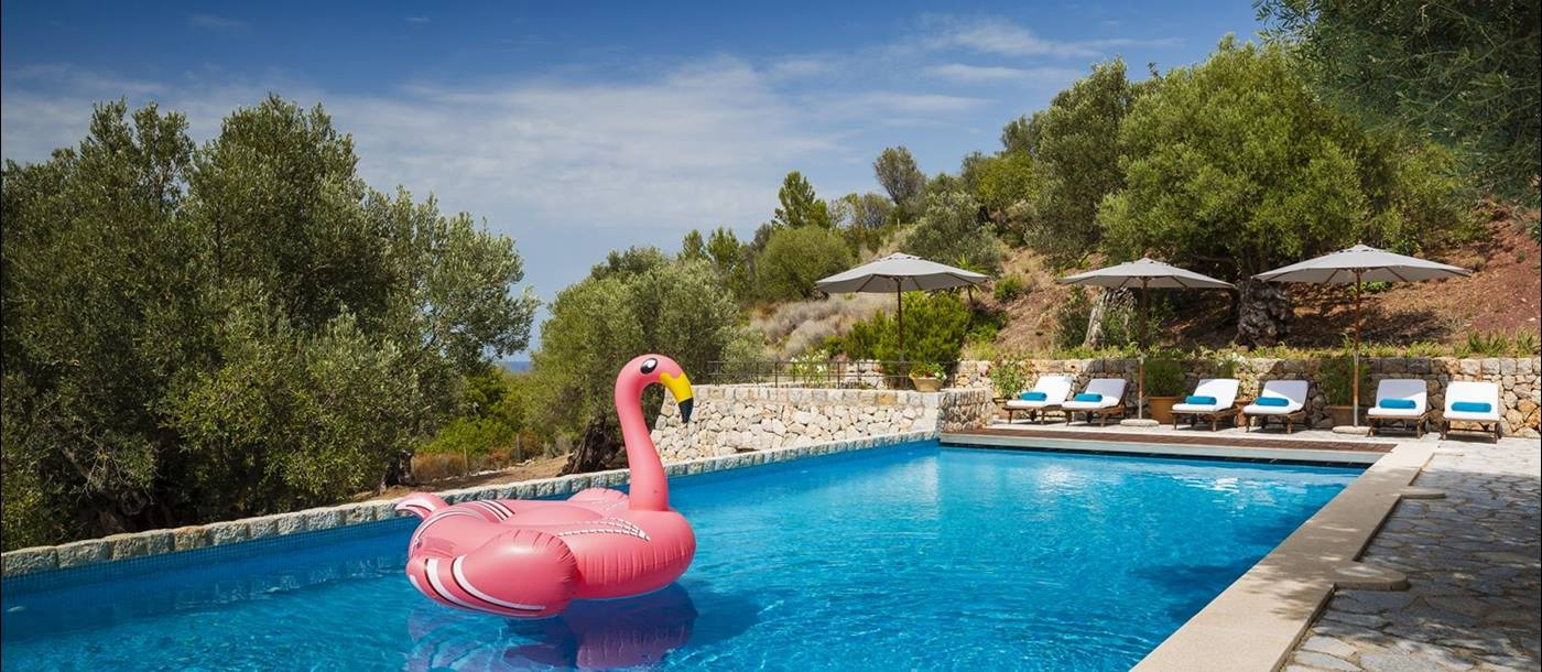 Swimmingpool with loungers, parasols and inflatable at luxury villa Sa Terra Rotja