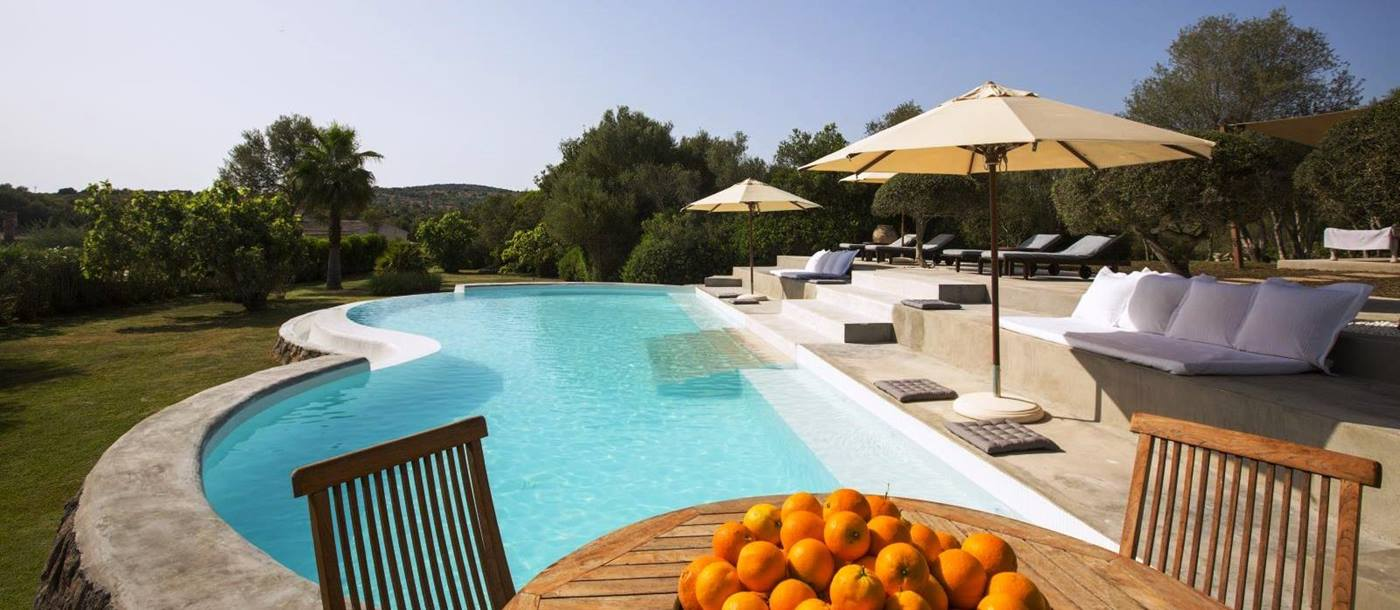 Curved swimming pool with pool furniture and table with big bowl of oranges at villa San Lorenzo in Mallorca