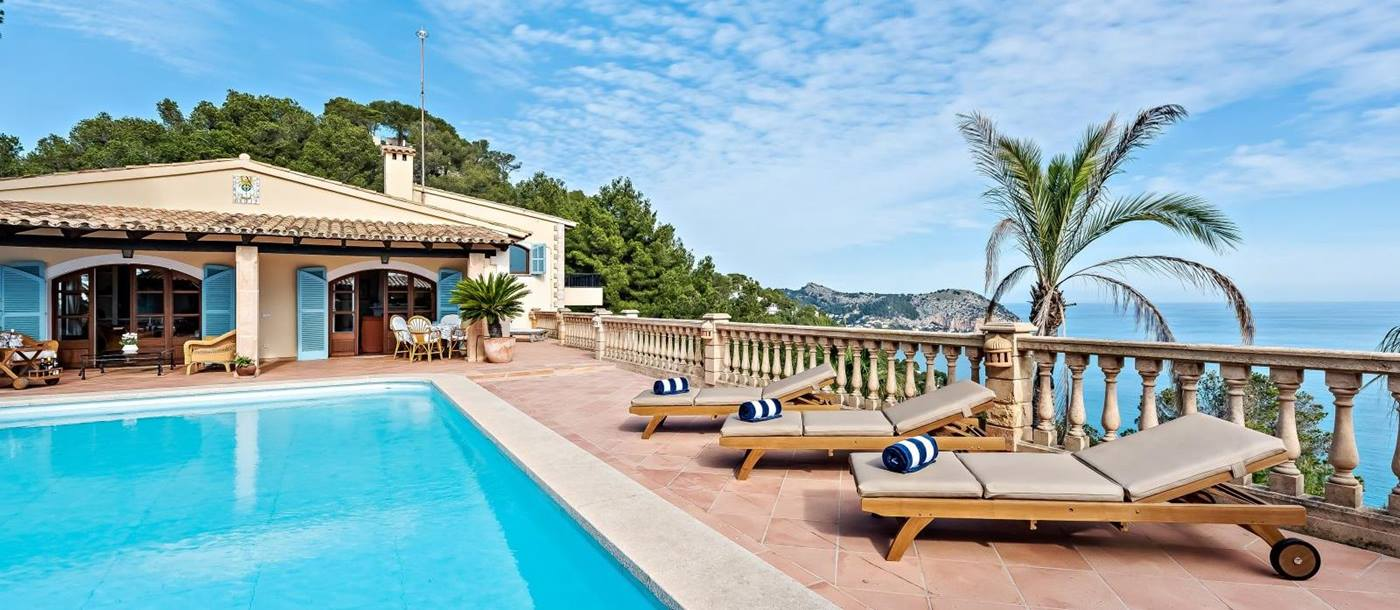 3 sunbeds with rolled up blue and white striped towels next to pool at villa canyamel in Mallorca, spain